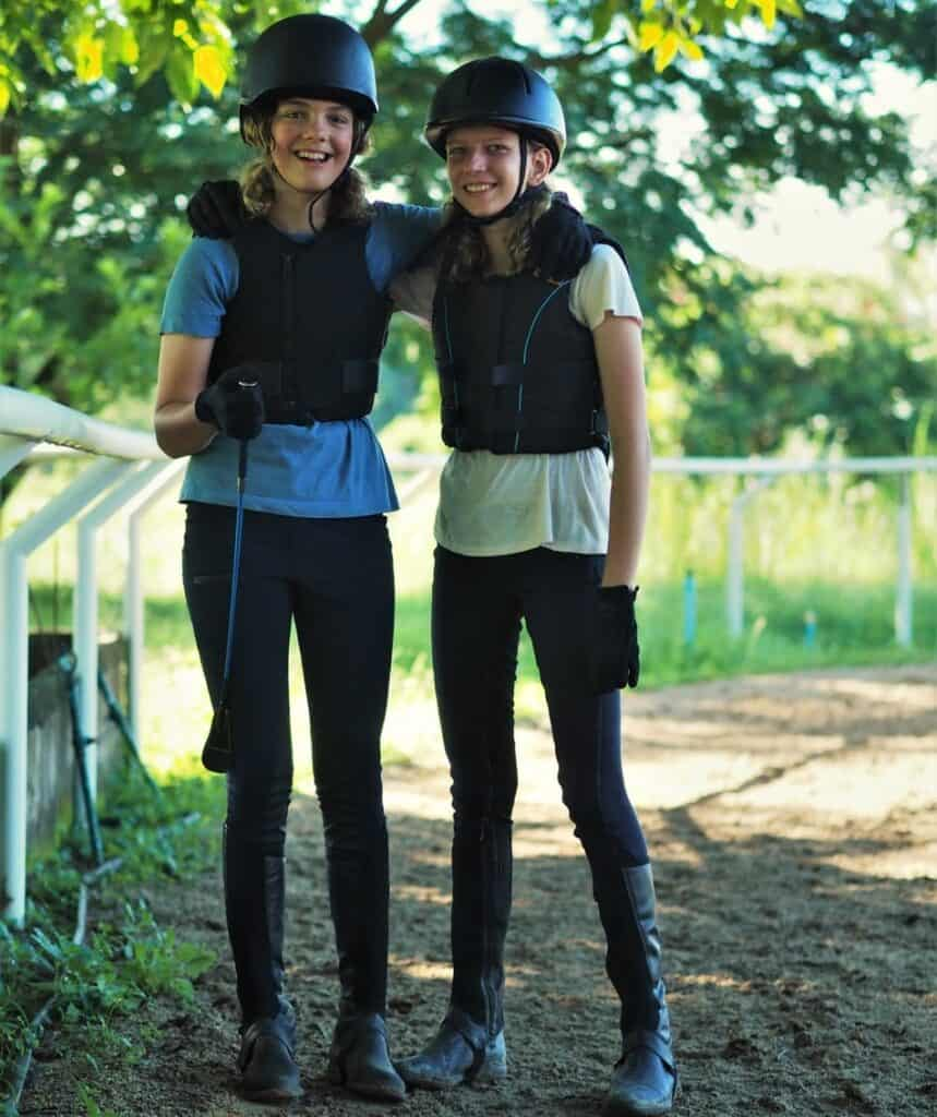 smiling girls wearing protective horse riding gear